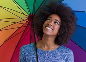 Smiling woman with rainbow umbrella