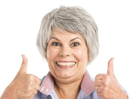 older woman smiling giving thumbs up