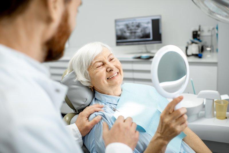 Senior woman smiling at reflection at dentist's office